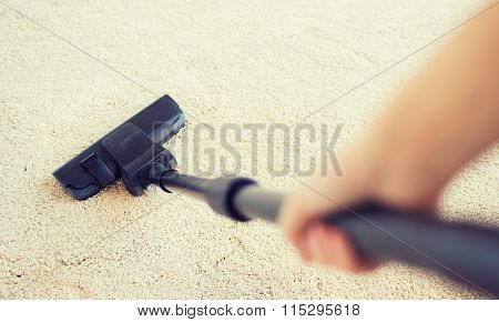 close up of hand with vacuum cleaner at home