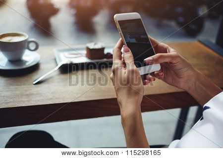 Hipster girl watching video on mobile phone during coffee break