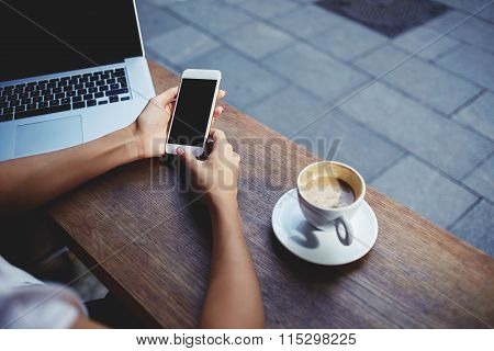 Female watching video on mobile phone during rest in coffee shop