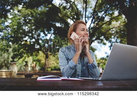 Young happy woman calling with smart phone while taking break between work on laptop computer