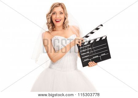 Joyful young bride in a white wedding dress holding a movie clapperboard isolated on white background