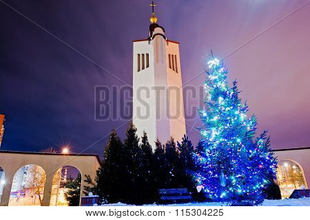 Church Bell With New Year Tree With Shining Garland At Moon Light At Frozen Evening
