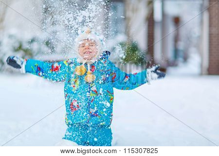 Little kid boy playing with snow in winter, outdoors