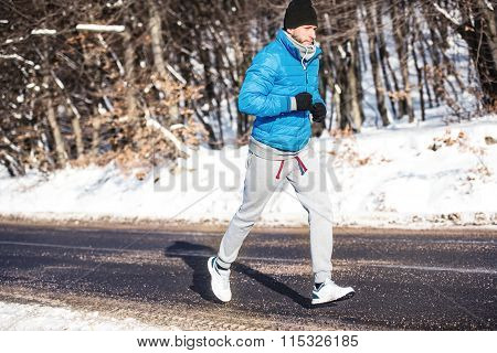 Young Athlete Going For A Run Outdoor In Snow, Hardcore Training And Jogging
