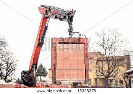 Crane Or Industrial Forklift Delivers A Brick Pallet At Building Construction Site