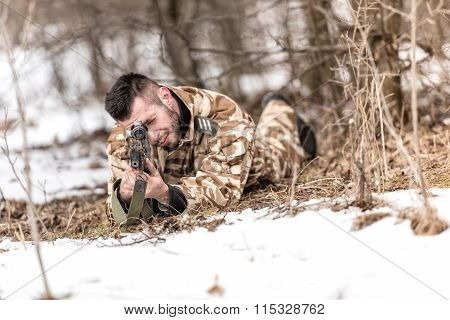 Military Man In Combat Uniform Holding A Gun And Shooting Outdoors. Hunting Or Military Concept
