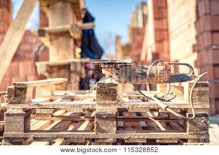 Angle Grinder Power Tool On Construction Site - Tools And Wooden Blocks At Building Site