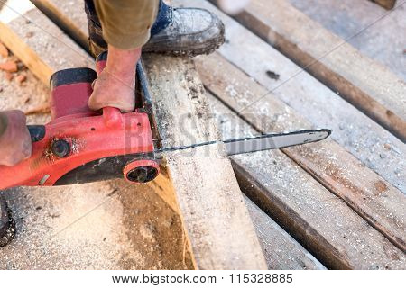 Worker Cutting Wooden Boards On Contruction Site With Electric Circular Saw