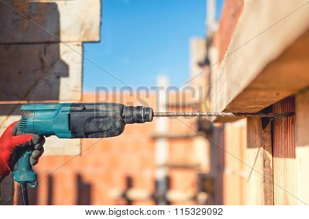 Worker On Construction Site Using Drilling Machine And Wire Rod At Building Walls