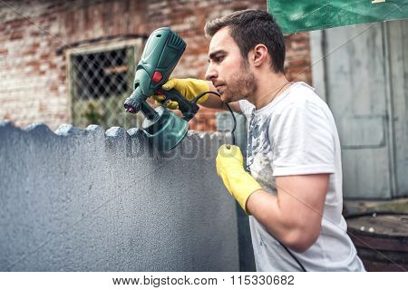 Professional Construction Worker Painting Walls At House Renovation. Exterior Building Renovation