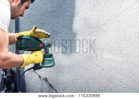 Man Painting A Grey Wall, Renovating Exterior Walls Of New House