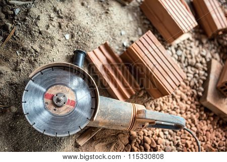 Angle Grinder Used On Construction Site For Cutting Bricks, Debris. Tools And Bricks On New Building