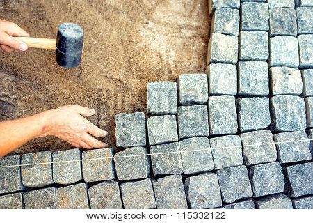 Industrial Worker Installing Pavement Rocks, Cobblestone Blocks On Road Pavement