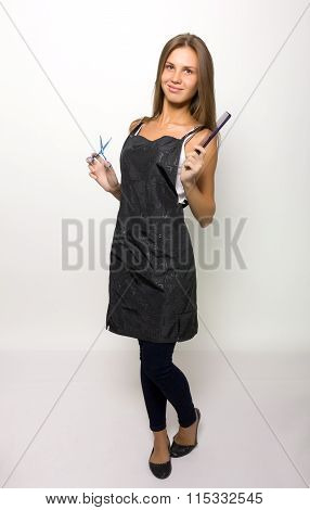 Very attractive and stylish professional hairdresser woman with scissors in right hand and comb in l