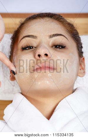 Hands of therapist apply cream to face of woman. Concept of care and youth