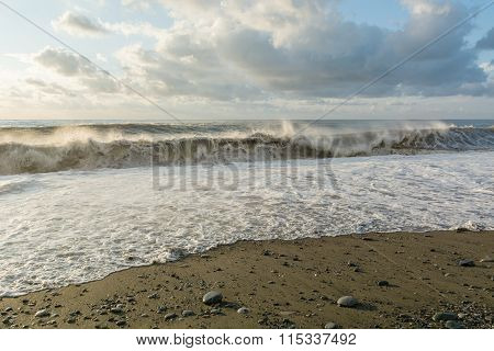huge waves washing the gravel beach