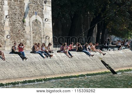 PARIS FRANCE - OCTOBER 9 2014: Parisians and tourists have picnic and relax on St Louis island. Seine embankment is popular spot for picnic and promenades at weekends. Paris France
