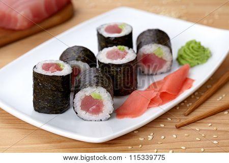 Maki sushi roll with tuna, wasabi, ginger and nori seaweed.