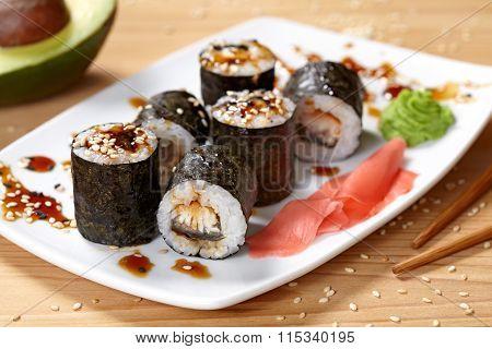 Maki sushi roll with eel, wasabi, ginger and nori seaweed.