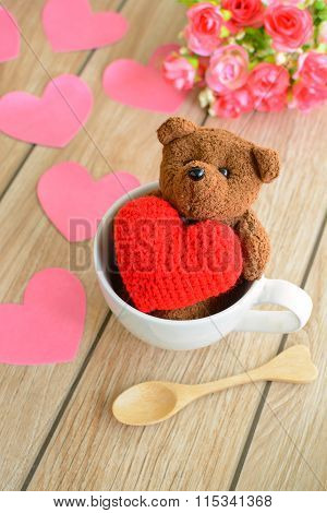 Teddy Bear In Cup Of Coffee With Red Heart Shape On Wooden Table