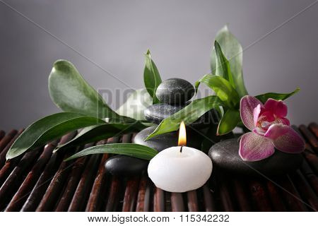 Spa still life with beautiful flower and candlelight on bamboo sticks closeup