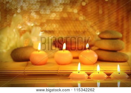 Spa still life with stones, candles and flowers in water on blurred lights background