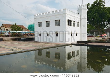 Exterior of the white historical building reflected in the water of the pond in Kuching, Malaysia.