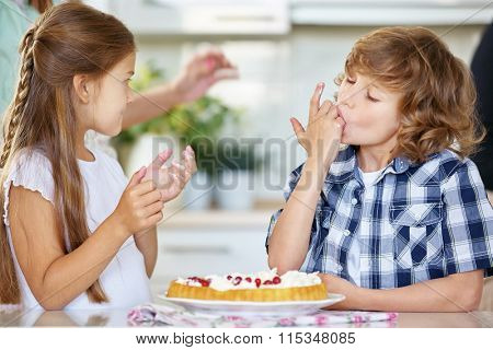 Two children tasting from red currant fruitcake in the kitchen