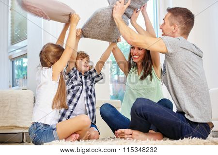 Family with two kids having fun and making a pillow fight at home
