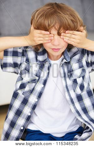 Boy playing hide and seek and covering his eyes with his hands at home