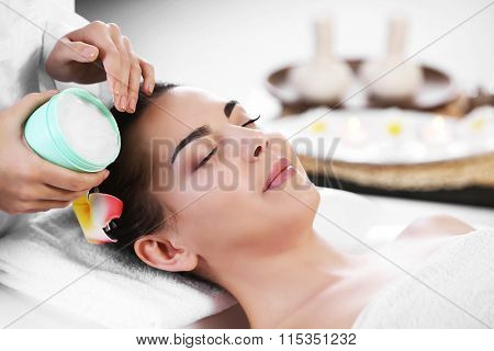 Masseur putting cream on woman's face during massage process at beauty spa