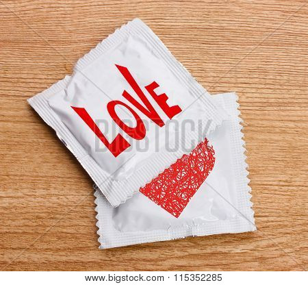 Condoms with text Love on wooden table