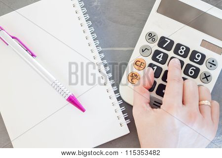 Hand With Calculator And Notepad