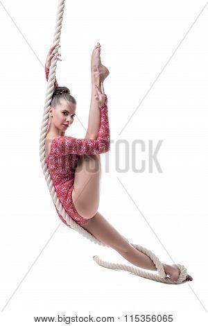 Charming barefoot girl posing hanging on rope