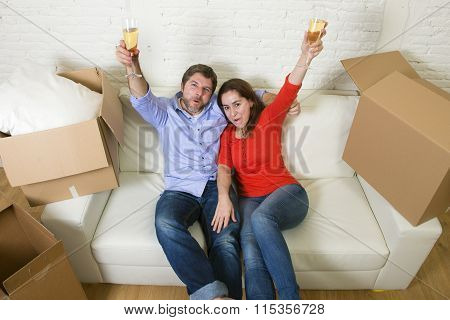 Happy American Couple Lying On Couch Together Celebrating Moving In A New House Or Apartment Flat