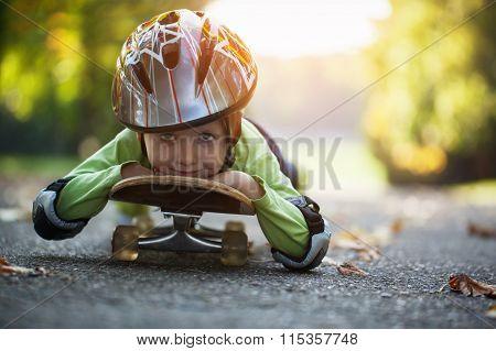 Little Boy Having Fun With Skateboard In The Helmet Outdoors.