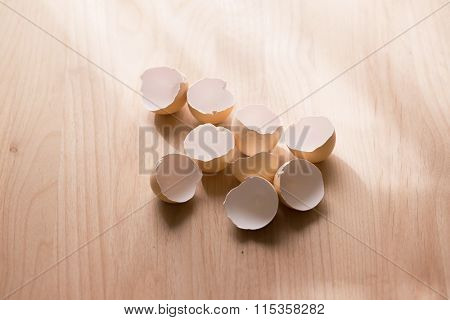 Open egg shells on wooden table. Shallow depth of field. intentionally shot with by the window like hard shadows.