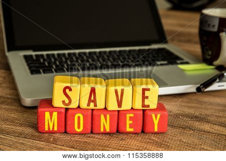Save Money written on a wooden cube in a office desk
