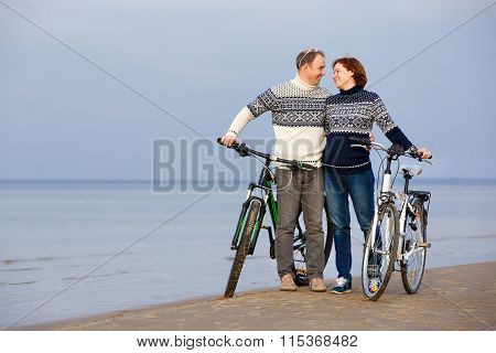 Cheerful couple biking on a sand beach