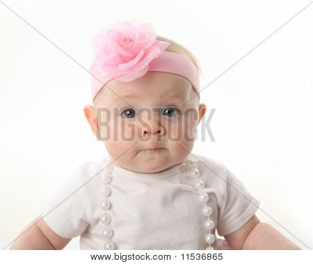 Close Up Portrait Of Pretty Baby Wearing Pearls