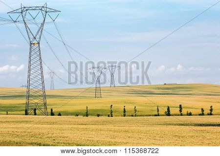 High-voltage towers and cables in agricultural fields