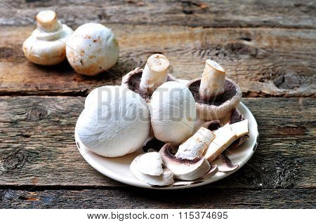 peeled and sliced mushrooms on a wooden background