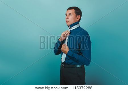 a man of European  appearance thirty years  straightens his tie