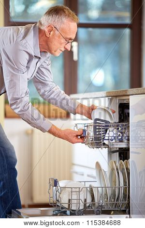 Mature Man Empty Out The Dishwasher