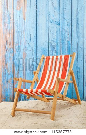 Red striped beach chair in sand