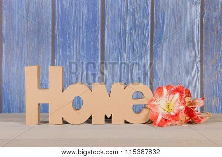 Word home with Amaryllis flowers on blue background