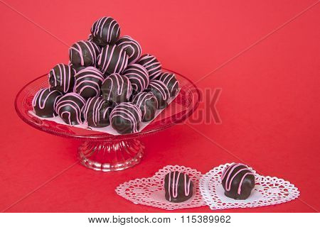 Chocolate cake balls stripped with pink candy melts stacked pyramid pattern