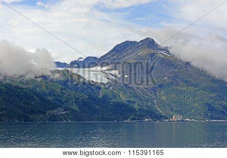 Glacier Above A Coastal Town