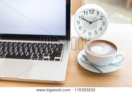 A Cup Of Coffee In A White Cup And Computer Labtop On Mable Table