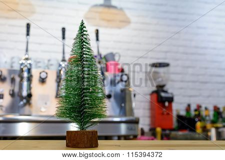 Small Green Christmas Tree In Wooden Support Over Restaurant Table. Artificial Christmas Evergreen T